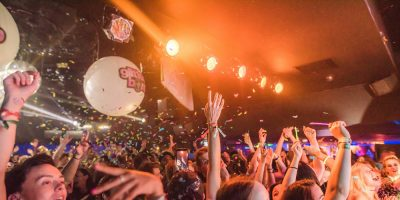 crowd with hands in the air at a glitterbomb events club night for lgbt+